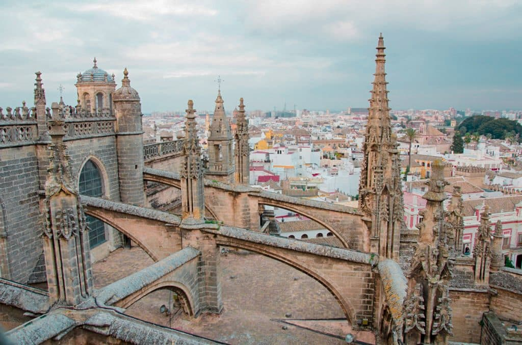 Seville Cathedral, one of the best things to do in Seville. Gothic church overlooking Spanish city skyline.