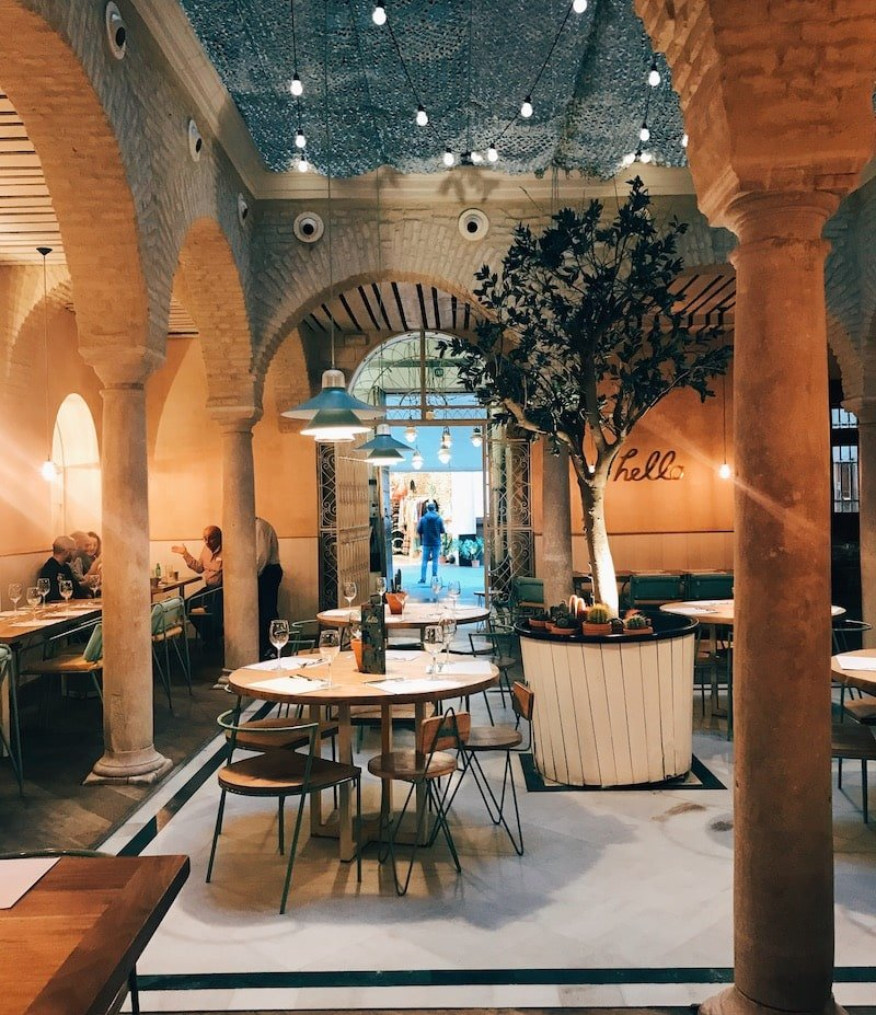 El Pinton, one of the best places for Sevilla tapas. Tapas bar with stone arches and hanging lights with round tables in Seville, Spain.