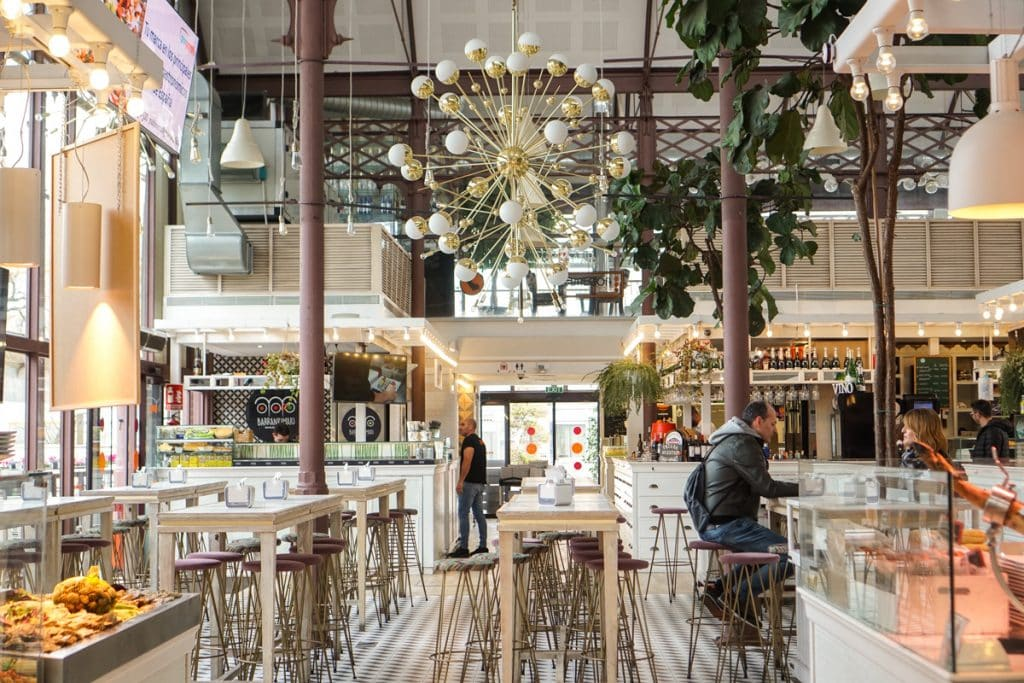 10 most iconic things to do in Seville. Mercado Lonja del Barranco gourmet food market with trendy decor in a glass building.